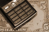 Mobile phone in dollars sepia — Stock Photo