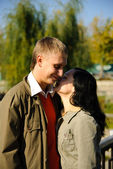 Young woman whispers to mans ear — Stock Photo