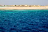 Yellow sand coastline in deep blue sea — Stock Photo