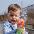 Stock Photo: Small boy playing with soap bubbles