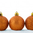 Three golden christmas balls in a snow — Stock Photo