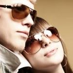 Fashionable young couple wearing sunglas — Stock Photo