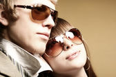 Fashionable young couple wearing sunglas — Stock Photo