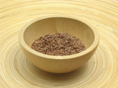 Wooden bowl with flaxseed on bamboo plat — Stock Photo