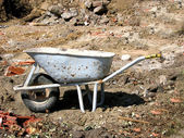 Cutout with a hand barrow on a site — Stock Photo