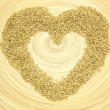 Bamboo plate with heart out of grain — Stock Photo
