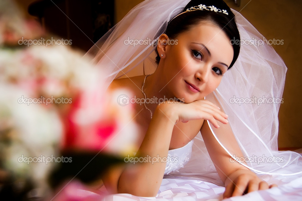 Portret of bride lying on the bed — Photo #1293137