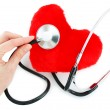 Hand with stethoscope checking a red hea -  