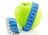 Bright green apple and measuring tape is — Stock Photo