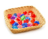 Colored assorted gemstones in wooden basket isol — Stock Photo