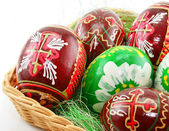 Group of painted Easter eggs in wooden basket (E — Photo