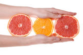 Hands holding sliced orange and grapefruit — Stock Photo