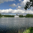 House on pond. White clouds on blue sky — Stock Photo