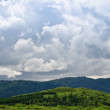 Pasture against mountains and clouds — Stock Photo