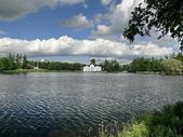 House on pond. White clouds on blue sky — Stok fotoğraf