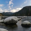 Big stones in river and clouds — Stock Photo