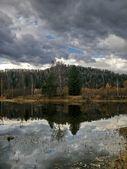 Heavy sky reflexion in dark lake — Stock Photo