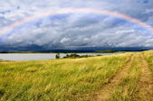 Field road and rainbow over lake — Stock fotografie