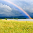 Stock Photo: Colors rainbow over lake and fields