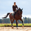Young girl riding on bay horse — Stock Photo