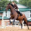 Training: young girl riding on bay horse — Stockfoto