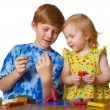 Boy and girl with plasticine - Stock Photo