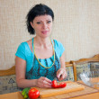 Stock Photo: Girl in the kitchen cut the vegetables