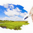 Hand with a brush paints a landscape — Stock Photo