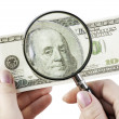 Stock Photo: One hundred dollars under magnifier