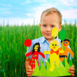 Royalty-Free Stock Photo: The boy against a green field with a fam