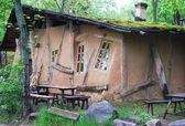 Unusual curve ancient hut in dark wood — Stock Photo