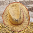 Old straw hat against a brick wall — Stock Photo