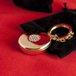 Elegant gold charm and black velvet bag — Stock Photo