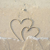 Two connected hearts drawn on wet sand — Stock Photo