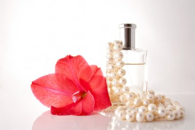 Bottle with perfume, a pearl necklace