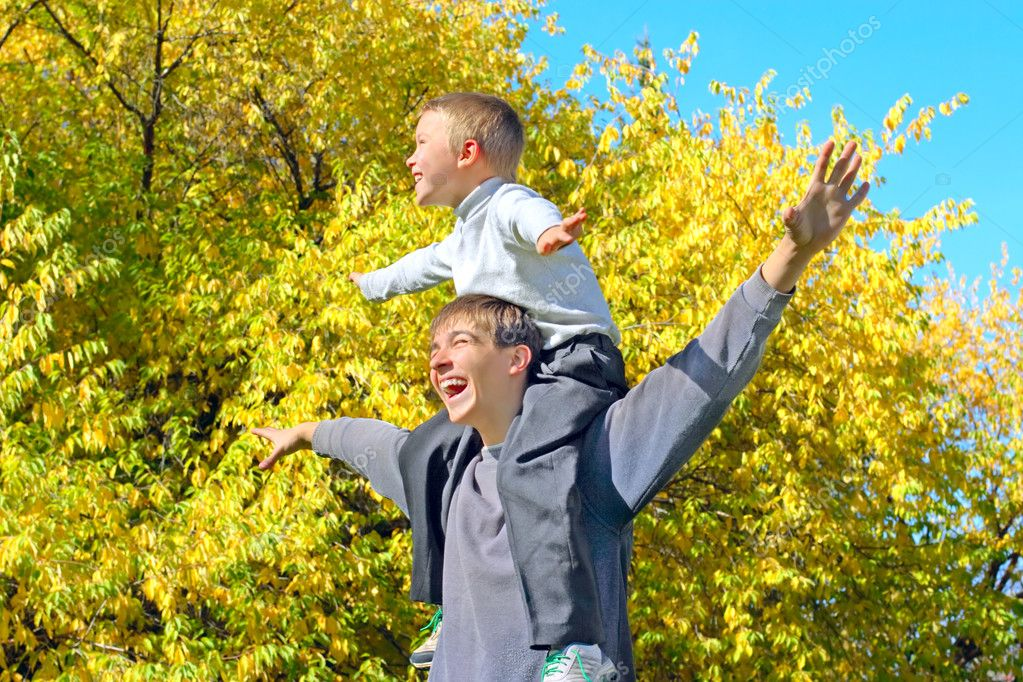 The happy child sits on the teenager shoulders  Stock Photo #1326996