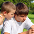 Teenager and kid with mobile phone — Stockfoto
