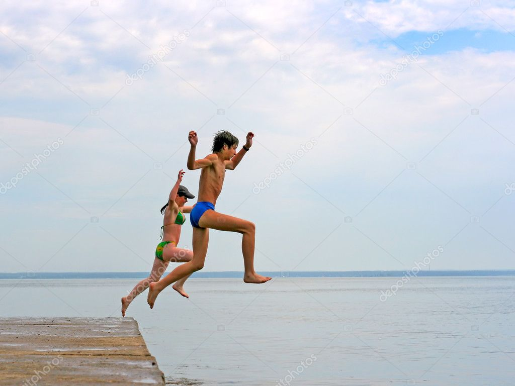 Two happy teenagers jumping in the sea — Stock Photo #1332416