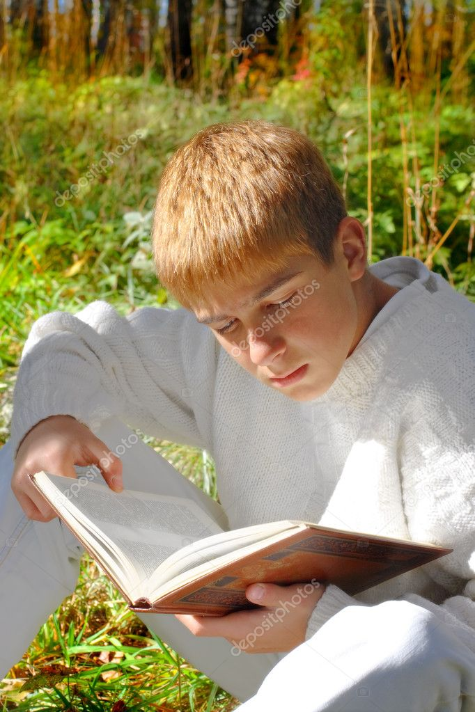 Reading boy sit in autumn forest with a book — Stock Photo #1792932