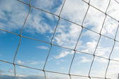 Blue cloudy sky through volleyball net — Stock Photo