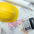 Hardhat, euros, calculator on blueprints — Photo