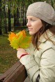 Woman in park with autumn leaves — Stok fotoğraf