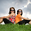 Friends sitting on the grass — Stock Photo