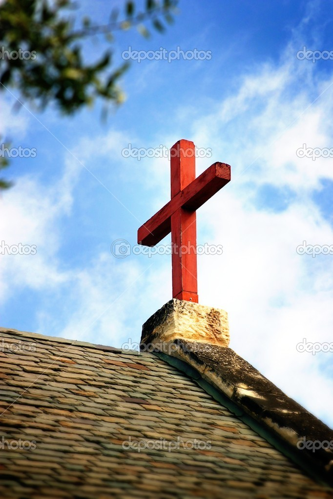 Cross on church roof top with a blue and white sky in background. — Stock Photo #2056767