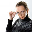 Serious woman looking over glasses — Stock Photo