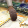 Well-used brush in over paintbox - Stock Photo