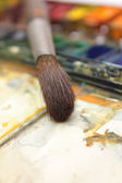 Well-used brush in over paintbox — Stock Photo