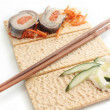 Chopsticks with fish rolls — Stock Photo