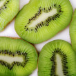 Stock Photo: Kiwi. Segments of kiwi on white glass