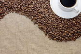 Cup from coffee on coffee grains — Stock Photo